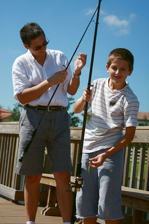Father and son fishing on pond