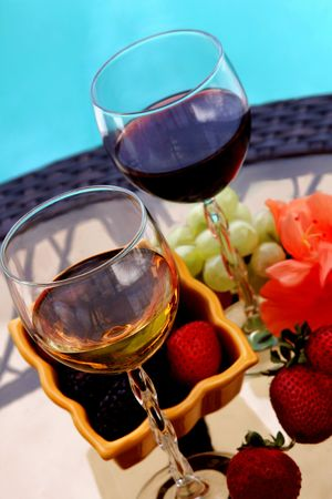 ifestyle: Different types of wine and berries by swiming pool