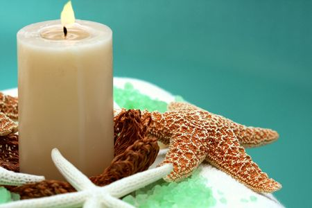 Candle and spa item on white towel