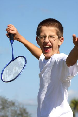 Boy playing badminton on a blue sky background Imagens