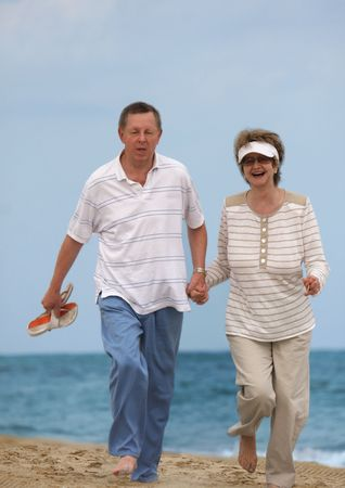 Romantic mature couple jogging at the beach photo