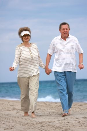 boomers: Romantic mature couple jogging  at the beach