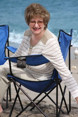 Mature woman relaxing on a sandy beach photo