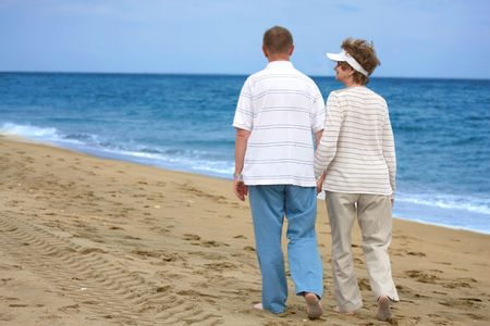 Romantic mature couple walking on the beach