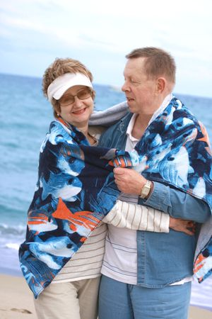 Couple at the beach hugging and smiling photo
