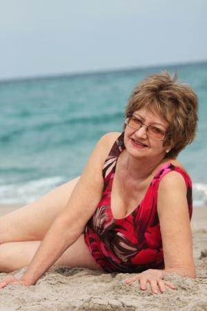 Oudere vrouw ontspannen op het strand Stockfoto