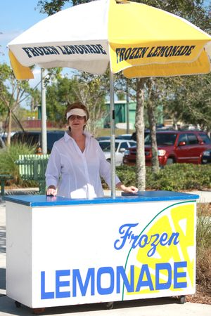 Senior woman at lemonade stand Imagens