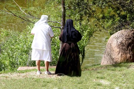 innocense: Back view of nuns relaxing in the garden Stock Photo