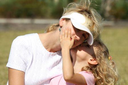 Little girl kissing her mother photo