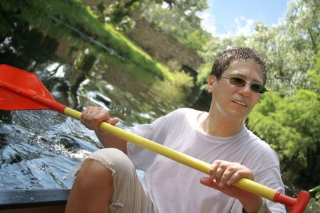 Kayak surfer paddling in rough river photo
