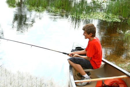 Boy fishing from the boat photo