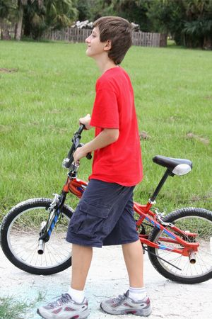 msn: Teenager boy walking with bicycle in the summer park