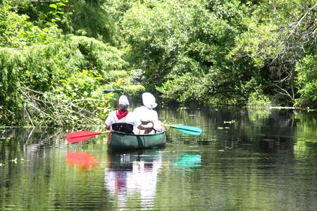 Couple kayaking in a wetland river Imagens