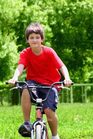 Teenager boy with bicycles in summer park