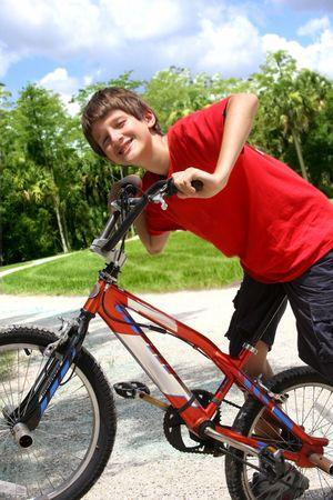 niños en bicicleta: Muchacho adolescente con bicicletas en el parque de verano