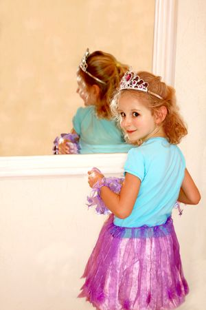 Cute little girl with crown costume looking to mirror