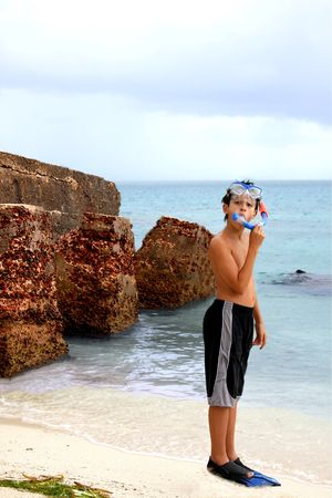 dry tortugas: Boy standing on the beach by the ocean, wearing flippers on his feet, goggles and a snorkel on his head.