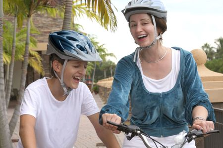 lifestile: Mother and son biking together in the city, laughter Stock Photo