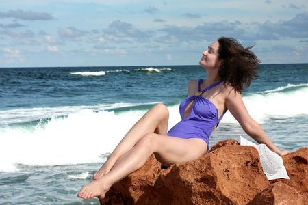 Woman on the rock by the sea