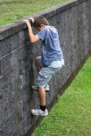 Boy climbing a wall of stones
