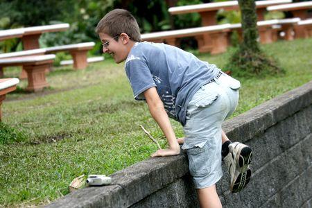 Boy climbing a wall of stones photo