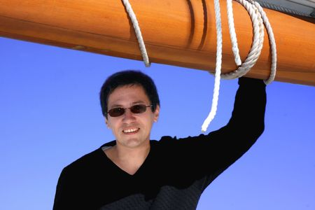 Handsome  man on boat, blue  sky with ship mast background