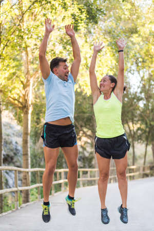 Athlete couple jumping with arms up in the park