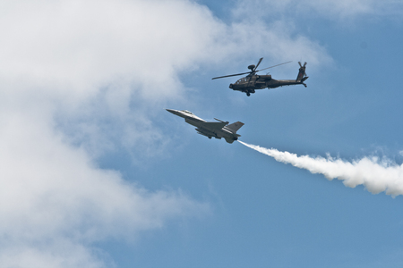 Changi, Singapore - Feb 6,2010 : A Republic of Singapore Air Force (RSAF) AH-64 Apache attack helicopter and an RSAF F-16C Fighting Falcon fighter jet fly in formation in Singapore Air Show 2010