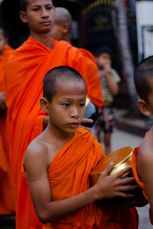 Kanchanaburi, Thailand - March 16, 2014: Young monk waiting for receive food from villagers in Sangkhlaburi, Thailand Editorial