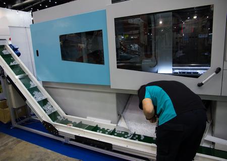 Worker operating bottle cap making machine