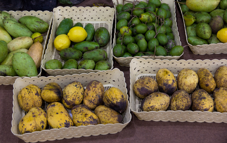 asian flavors: Different kind of mangoes and limes in plastic trays