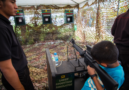Bangkok, Thailand - January 13, 2018: Asian boy shoot laser simulator machine gun in Thai Army base open to public in Childrens Day 2018 Editorial