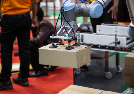 The Universal Robot  collaborative industrial robot arm lifing box