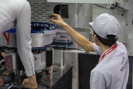 Bangkok, Thailand - November 21, 2018: Worker operate Dual motion parts feeder machine in Metalex 2018 報道画像