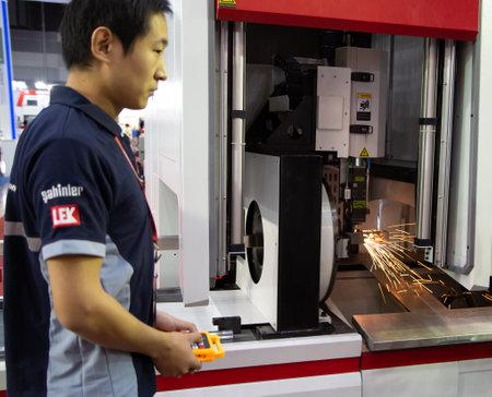 Bangkok, Thailand - November 23, 2018: Operator control CNC laser cutting machine cutting tube in Metalex 2018