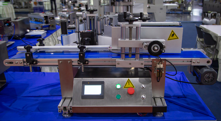 Vertical round bottle labeling machine for food industry Stock Photo