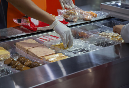 Worker put food in plastic tray for packing food in machine Stockfoto