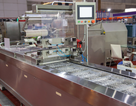 Linear tray food heat sealing and packaging machine Фото со стока
