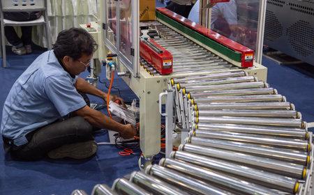 Bangkok, Thailand - February 13, 2019: Worker repair carton packing machine on roller conveyor in Food Pack Asia 2019