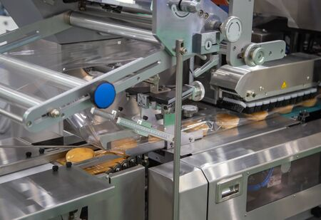 Bread, toast, bun plastic wrapping machine on bakery production line