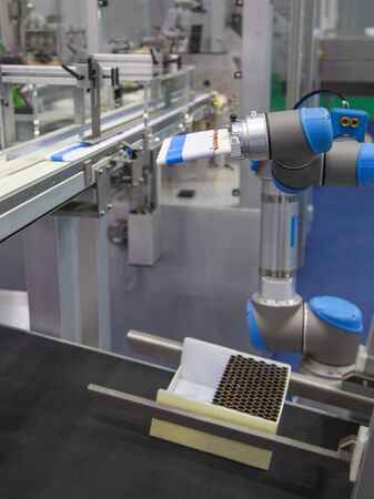Automation robotic arm load aluminum tube to filling machine in production line Banque d'images
