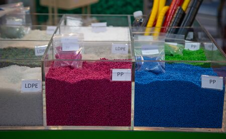 Colorful of dyed plastic polymer granules in containers