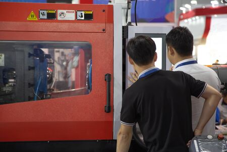 worker operating industrial plastic injection molding press machine for manufacturing Stok Fotoğraf - 128185929
