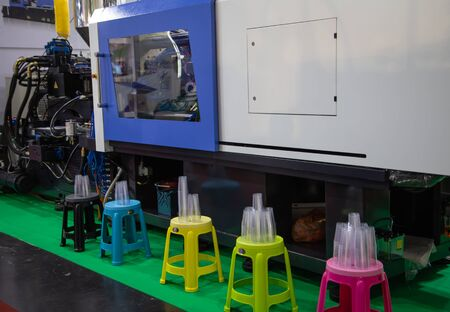Disposable plastic cup product from plastic injection molding press machine Stok Fotoğraf - 128185923