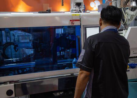 Trabajador que opera la máquina industrial de la prensa del moldeo por inyección de plástico para la fabricación Foto de archivo