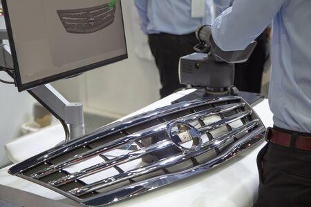 Industry worker use handheld 3D scanner inspecting car grille