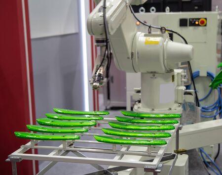 Bras robotique peignant des pièces de moto dans l'industrie automobile
