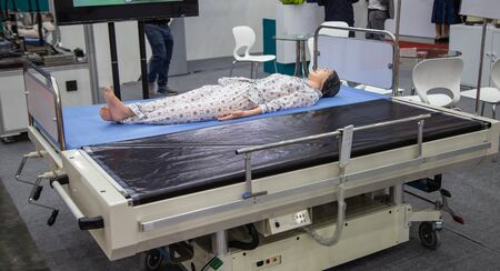 Patient dummy lying on automatic transfer hospital bed