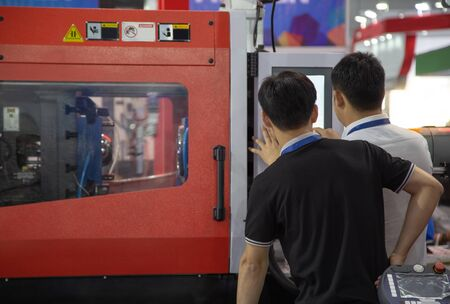worker operating industrial plastic injection molding press machine for manufacturing Stok Fotoğraf