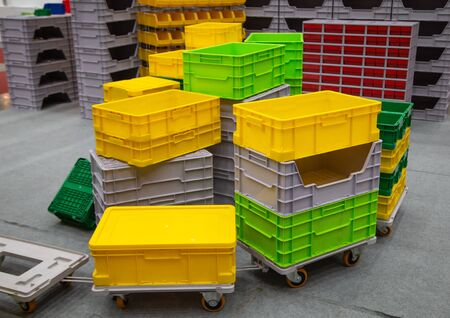 Stack of colorful empty plastic crate on trolley